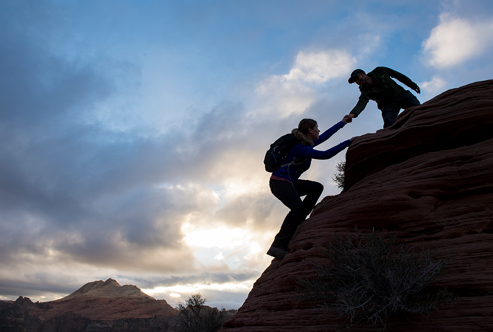 Hikers helping each other near Tabernacle Dome on the Kolob Terrace in Zion National Park.