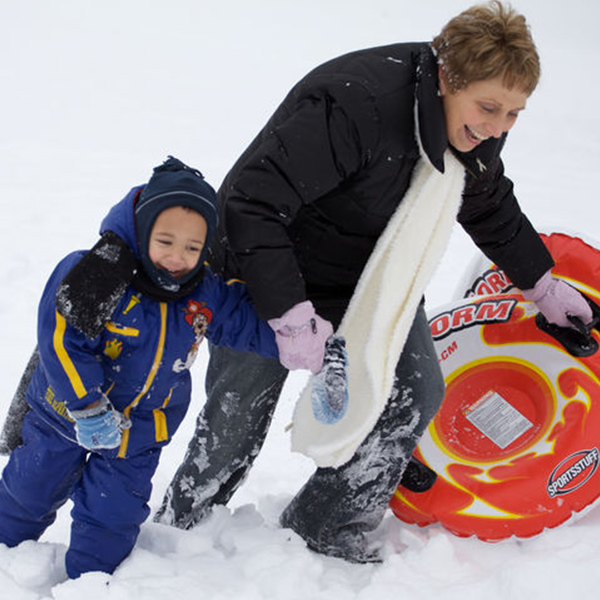 A woman and toddler trudge up a snowy hill